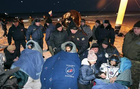 The International Space Station (ISS) crew members Japanese astronaut Akihiko Hoshide (L), Russian cosmonaut Yuri Malenchenko (C) and U.S. astronaut Sunita Williams rest after landing near the town of Arkalyk in northern Kazakhstan November 19, 2012. REUTERS/Maxim Shipenkov/Pool