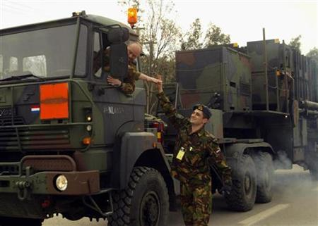 A Dutch army officer bids farewell to a Dutch driver as a convoy of Dutch army trucks carrying Patriot missile systems leave a Turkish navy base in southern Turkish port city of Iskenderun February 27, 2003. REUTERS/Fatih Saribas/Files