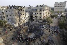 Israel bombardeó el lunes decenas de supuestos sitios de combatientes en la Franja de Gaza gobernada por Hamás y el fuego de cohetes palestinos desde el enclave declinó después de que se intensificaron los esfuerzos internacionales por negociar una tregua. En la imagen, varios palestinos se reúnen en torno a una casa destruida en Jan Yunis, en el sur de la Franja de Gaza, el 19 de noviembre de 2012. REUTERS/Ibraheem Abu Mustafa