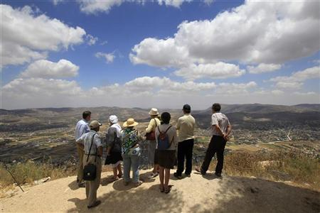 Tourists stand at a lookout point on Mount Gerizim, overlooking the West Bank city of Nablus, during a tour of Jewish settlements in the West Bank June 13, 2011. REUTERS/Ronen Zvulun