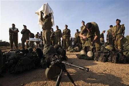 Israeli soldiers pray next to their gear near the border with the Gaza Strip November 19, 2012. REUTERS/Nir Elias