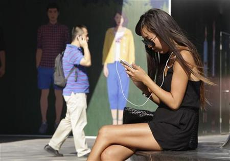 A woman checks her iPhone outside an Apple store in Beijing August 24, 2012. REUTERS/Jason Lee/Files
