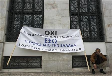 A protester smokes as he takes part in a rally organised by municipality workers against state sector layoffs demanded by the country's international lenders, outside the city hall in Athens November 19, 2012. REUTERS/John Kolesidis (GREECE)