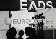 Visitors talk near the welcome desk of the EADS booth at the ILA Berlin Air Show in Selchow near Schoenefeld south of Berlin on September 13, 2012. REUTERS/Tobias Schwarz (GERMANY ENTERTAINMENT - Tags: TRANSPORT BUSINESS)
