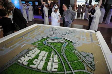 People stand near a scale model of an expanded facility of the Abu Dhabi International Airport during the World Route Development Strategy Summit at Abu Dhabi National Exhibition Centre, September 30, 2012. REUTERS/Ben Job