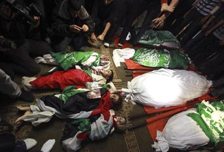 ATTENTION EDITORS - VISUAL COVERAGE OF SCENES OF DEATH OR INJURY Palestinians surround the bodies of members of the al-Dalo family during their funeral at a mosque in Gaza City November 19, 2012. Nine members of the al-Dalo family, including four children, were killed in an Israeli strike on their house on Sunday, Palestinian medics said. REUTERS/Mohammed Salem