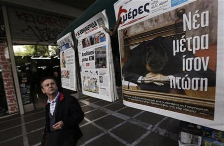 A man walks past a newspaper featuring Greek Prime Minister Antonis Samaras in central Athens November 15, 2012. REUTERS/John Kolesidis