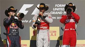 O inglês Lewis Hamilton, da McLaren, o alemão Sebastian Vettel (E), da Red Bull e o espanhol Fernando Alonso, da Ferrari bebem champagne após o Grande Prêmio de F1 em Austin, Texas. A Red Bull comemorou no Grande Prêmio dos EUA a conquista do tricampeonato consecutivo de construtores da Fórmula 1, no domingo, apesar de outro tricampeonato ter ficado na espera, o de Sebastian Vettel. 18/11/2012 REUTERS/Adrees Latif