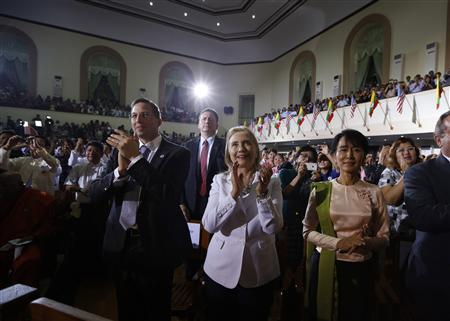 U.S. Secretary of State Hillary Clinton and Myanmar's Opposition Leader Aung San Suu Kyi (R) applaud in the audience as President Barack Obama (not pictured) arrives to deliver remarks at the University of Yangon, November 19, 2012. President Obama became the first serving U.S. president to visit Myanmar on Monday, trying during a whirlwind six-hour trip to strike a balance between praising the government's progress in shaking off military rule and pressing for more reform. REUTERS/Jason Reed