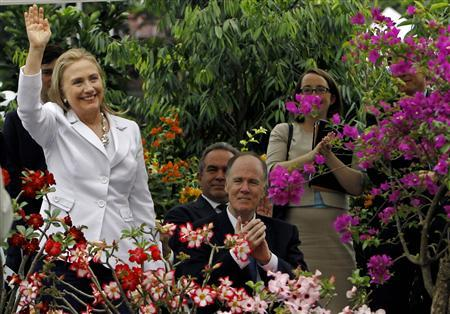 U.S. Secretary of State Hillary Clinton waves as U.S. President Barack Obama mentions her name, during a news conference with Myanmar's opposition leader Aung San Suu Kyi, after their meeting at Suu Kyi's residence in Yangon November 19, 2012. REUTERS/Soe Zeya Tun