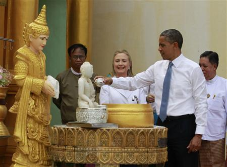 U.S. President Barack Obama pours water over a statue at a shrine as U.S. Secretary of State Hillary Clinton smiles during their visit to the Shwedagon Pagoda in Yangon November 19, 2012. Obama became the first serving U.S. president to visit Myanmar on Monday, trying during a whirlwind six-hour trip to strike a balance between praising the government's progress in shaking off military rule and pressing for more reform. REUTERS/Jason Reed