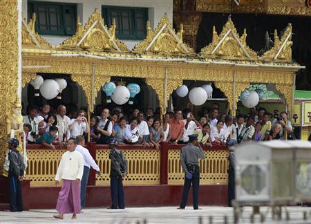 Foreign tourists and locals watch as U.S. President Barack Obama and Secretary of State Hillary Clinton (not pictured) tour the Shwedagon Pagoda in Yangon November 19, 2012. Obama became the first serving U.S. president to visit Myanmar on Monday, trying during a whirlwind six-hour trip to strike a balance between praising the government's progress in shaking off military rule and pressing for more reform. REUTERS/Jason Reed