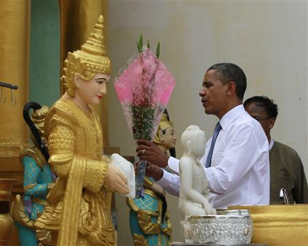 U.S. President Barack Obama places a floral offering at a shrine during his visit to the Shwedagon Pagoda in Yangon November 19, 2012. Obama became the first serving U.S. president to visit Myanmar on Monday, trying during a whirlwind six-hour trip to strike a balance between praising the government's progress in shaking off military rule and pressing for more reform. REUTERS/Jason Reed