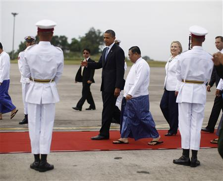 U.S. President Barack Obama speaks with an unidentified official as U.S. Secretary of State Hillary Clinton follows behind upon their arrival at Yangon International Airport November 19, 2012. Obama has become the first serving U.S. president to visit Myanmar, arriving on Monday for a trip that will attempt to strike a balance between praising the government's progress in shaking off military rule and pressing it for further reforms. REUTERS/Jason Reed