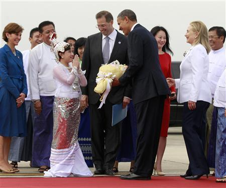A girl gestures after presenting U.S. President Barack Obama (4th R) with a bouquet of flowers upon his arrival at Yangon International Airport November 19, 2012. Obama has become the first serving U.S. president to visit Myanmar, arriving on Monday for a trip that will attempt to strike a balance between praising the government's progress in shaking off military rule and pressing it for further reforms. U.S. Secretary of State Hillary Clinton (2nd R) smiles behind Obama. REUTERS/Jason Reed