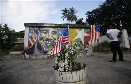 A U.S. flag is pictured in a pot of plants near a graffiti depicting U.S. President Barack Obama in Yangon November 19, 2012. Poised to become the first U.S. head of state to travel to Myanmar, Obama on Monday will attempt to strike a balance between praising the government's progress in shaking off military rule and pressing it for further reforms. REUTERS/Soe Zeya Tun
