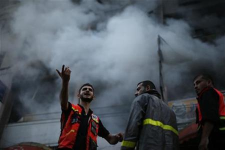 A Palestinian firefighter gestures next to his colleagues as smoke rises out of a building that also houses international media offices, after an Israeli air strike witnessed by a Reuters journalist, in Gaza City November 19, 2012. An Islamic Jihad local commander was killed on Monday in an Israeli air strike on a tower block that houses many international media, a source in the militant group said. REUTERS/Suhaib Salem (GAZA - Tags: MILITARY CONFLICT MEDIA)