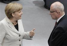 German Chancellor Angela Merkel talks to CDU faction leader Volker Kauder(R) before the start of a session of the Bundestag, German lower house of parliament, at the Reichstag in Berlin September 12, 2012. Germany's Constitutional Court gave a green light on Wednesday for the country to ratify the euro zone's new rescue fund and budget pact but gave parliament veto powers over any future increases in the size of the fund.The eagerly anticipated verdict by the court in Karlsruhe, southern Germany, boosted global stocks and the euro currency as investors breathed a sigh of relief that the euro zone's rescue fund could take effect after months of delay. REUTERS/Tobias Schwarz (GERMANY - Tags: BUSINESS POLITICS)