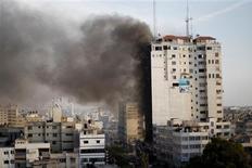 """Misiles israelíes impactaron el lunes por segundo día consecutivo en un edificio en Gaza que alberga a varios periodistas extranjeros, causando la muerte de dos personas, entre ellos un militante que el grupo Yihad Islámica dijo que había estado a cargo de una """"guerra mediática"""" contra Israel. En laimagen, humo saliendo de un edificio tras un ataque aéreo israelí, presenciado por un periodista de Reuters, en un edificio que acoge oficinas de medios en Gaza, el 19 de noviembre de 2012. REUTERS/Ahmed Jadallah"""