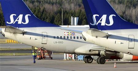 A technician walks under the tail of an SAS Boeing 737 aircraft at Stockholm Arlanda airport's Terminal Four, north of Stockholm November 12, 2012. REUTERS/Johan Nilsson/Scanpix