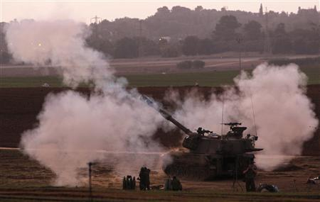 Israeli soldiers stand near a mobile artillery unit after it fired a shell towards northern Gaza from its position outside the Gaza Strip November 19, 2012. REUTERS/Amir Cohen