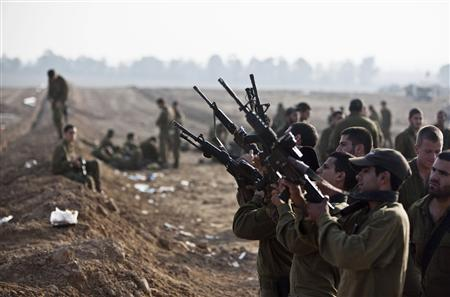 Israeli soldiers check their weapons at a staging area near the border with the Gaza Strip November 19, 2012. REUTERS/Nir Elias