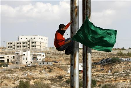 Palestinian stone-throwers holds a Hamas flag as he climbs a street pole during clashes with Israeli security forces outside Ofer prison near the West Bank city of Ramallah November 18, 2012. The clashes broke out following a protest against Israel's military operation in the Gaza Strip. REUTERS/Mohamad Torokman