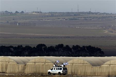 Hasidic Jewish men, from the Breslov sect, ride on a van with Israeli flags during a visit to support the soldiers, near the border with the Gaza Strip (seen in the background) November 19, 2012. REUTERS/Yannis Behrakis