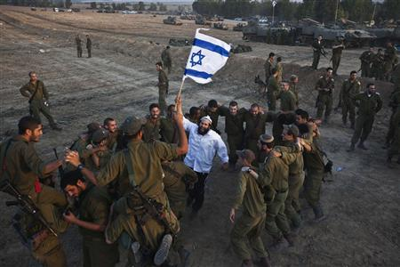 A Hasidic Jewish man, from the Breslov sect, holds an Israeli flag as he dances with Israeli troops during a visit to support the soldiers, near the border with the Gaza Strip November 19, 2012. REUTERS/Nir Elias