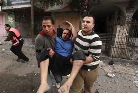 Palestinians evacuate a wounded man after an Israeli air strike, witnessed by a Reuters journalist, on a floor in a building that also houses media offices in Gaza City November 19, 2012. REUTERS/Mohammed Salem