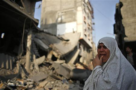 A Palestinian woman reacts in front of a destroyed house after an Israeli air strike in Gaza City November 19, 2012. REUTERS/Mohammed Salem