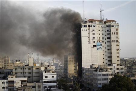 Smoke is seen after an after an Israeli air strike, witnessed by a Reuters journalist, out of a floor in a building that also houses media offices in Gaza City November 19, 2012. An Islamic Jihad local commander was killed on Monday in an Israeli air strike on a tower block that houses many international media, a source in the militant group said. REUTERS/Ahmed Jadallah