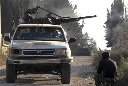 Members of the Free Syrian Army ride on the back of a truck during clashes in the town of Atareb November 17, 2012. REUTERS/Abdalghne Karoof