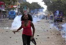 A female rioter runs away after throwing stones at the police during the second day of skirmishes in the Eastleigh neighbourhood of Kenya's capital Nairobi, November 19, 2012. Police fired tear gas to disperse Kenyans who threw stones and broke into the homes and shops of ethnic Somalis in Nairobi's Somali-dominated Eastleigh neighbourhood on Monday to protest against a bomb attack in the district on Sunday. REUTERS/Thomas Mukoya