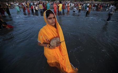 A Hindu devotee prays while standing in the waters of the Arabian Sea as she worships the Sun god during the Hindu religious festival 'Chhat Puja' in Mumbai, November 19, 2012. REUTERS/Vivek Prakash
