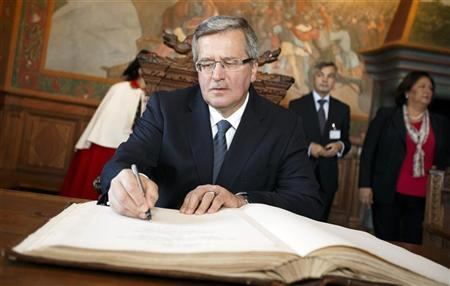 Poland's President Bronislaw Komorowski signs a guest book as he visits the castle of the village of Gruyeres October 5, 2012. REUTERS/Valentin Flauraud