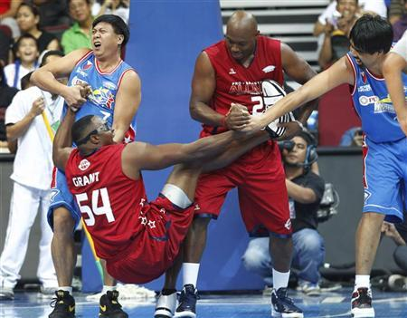 Former NBA player Horace Grant gets help from Mitch Richmond (2nd R) during a exhibition game with Philippine Basketball Association (PBA) star players inside the Mall of Asia Arena in Manila July 18, 2012. REUTERS/Romeo Ranoco