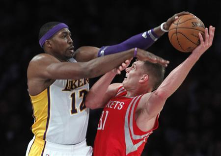 Los Angeles Lakers center Dwight Howard (12) blocks a shot by Houston Rockets center Cole Aldrich (R) during the second half of their NBA basketball game in Los Angeles, California November 18, 2012. Lakers won the game 119-108. REUTERS/Alex Gallardo