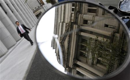 The Bank of Japan (BOJ) building is reflected in a mirror as a man walks past in Tokyo November 19, 2012. REUTERS/Toru Hanai