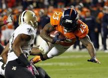 Denver Broncos running back Willis McGahee (23) flies to the 1-yard-line past New Orleans Saints cornerback Jabari Greer (L) in the first quarter of their NFL football game in Denver October 28, 2012. REUTERS/Rick Wilking