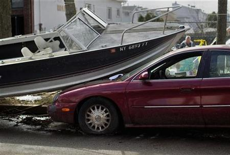 A boat is seen on top of an automobile damaged by superstorm Sandy in the Staten Island borough of New York November 14, 2012. REUTERS/Shannon Stapleton