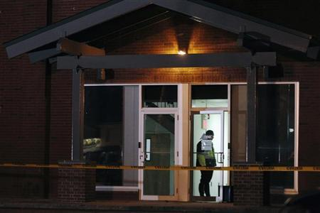A Framingham police officer (in doorway) keeps watch as federal agents search th New England Compounding Center company in Framingham, Massachusetts October 16, 2012. REUTERS/Dominick Reuter