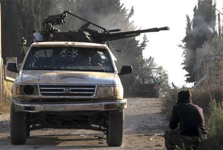 Members of the Free Syrian Army ride on the back of a truck during clashes in the town of Atareb November 17, 2012. Picture taken November 17, 2012. REUTERS/Abdalghne Karoof