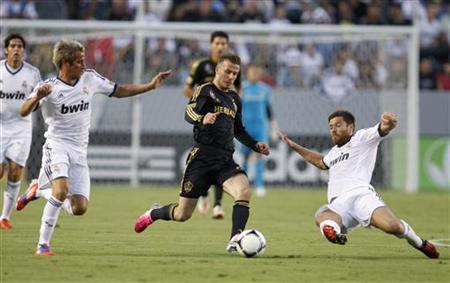 Los Angeles Galaxy's David Beckham (C) chases the ball between Real Madrid's Fabio Coentrao (L) and Xabi Alonso (R) during the first half of their World Football Challenge international friendly soccer match in Carson, California August 2, 2012. REUTERS/Danny Moloshok