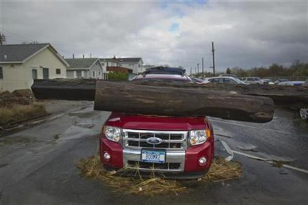 A log is seen on top of an automobile damaged by superstorm Sandy in the Breezy Point section of the Queens borough of New York October 30, 2012. REUTERS/Shannon Stapleton