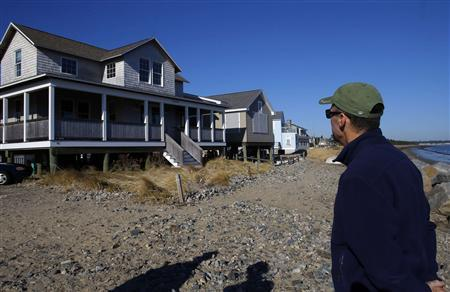 City Planning Director Bob Hamblen looks at a house which has been raised to minimize storm and flooding damage on the ocean's edge in Saco, Maine November 19, 2012. In the aftermath of the historic floods caused by Superstorm Sandy, some city leaders have begun to argue for the construction of sea walls capable of shielding the U.S. coastline from ever more intense storms. But in Saco, Maine, storm protection comes in a far less glamorous package. Along what used to be Surf Street, owners of beachfront houses are jacking their homes up to allow storm surges from Saco Bay to flow underneath them. REUTERS/Brian Snyder