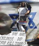 Protesters hold placards as they burn a mock Israeli flag during a rally outside the Israeli embassy in Manila's Makati financial district, November 20, 2012. About two dozen demonstrators in the Philippines gathered to protest against the Israeli-Gaza conflict that has resulted in the deaths of more than 100 people. REUTERS/Cheryl Ravelo (PHILIPPINES - Tags: CIVIL UNREST POLITICS)