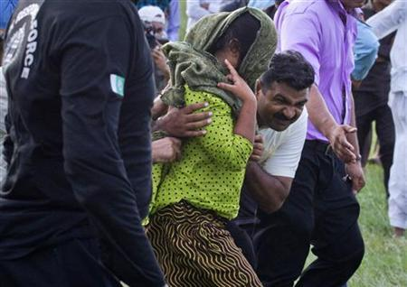 Security officials surrounding Rimsha Masih, (C, green scarf) a Christian girl accused of blasphemy, move her to a helicopter after her release from Adyala jail in Rawalpindi September 8, 2012.REUTERS/Stringer