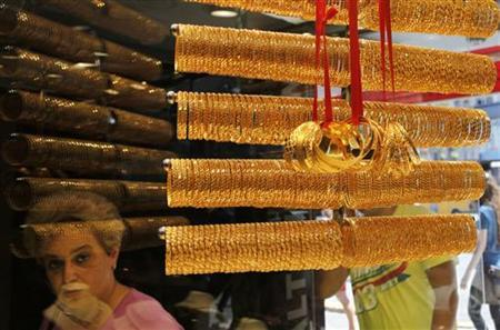 A customer is reflected in the window of a jewellery shop where gold bangles are on display in Istanbul August 23, 2011. REUTERS/Murad Sezer/Files