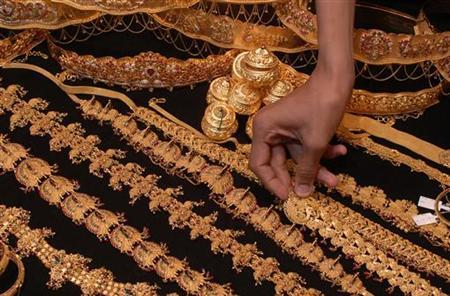 A salesman arranges gold jewellery at a shop in Hyderabad January 10, 2008. REUTERS/Krishnendu Halder/Files
